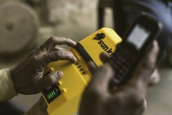 A customer using mobile money to pay  for his Sun King EasyBuy solar home system.jpg